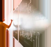 Imagem com um professor ao fundo escrevendo na lousa em foco